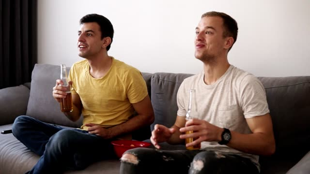 Two-excited-adult-men-drinking-beer-and-watching-football-game-indoor-on-tv-set-Celebrating-the-win-Close-up
