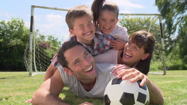 Family-Playing-Football-In-Garden-Together
