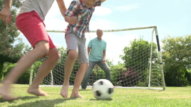Grandfather-Grandson-And-Father-Playing-Football-In-Garden