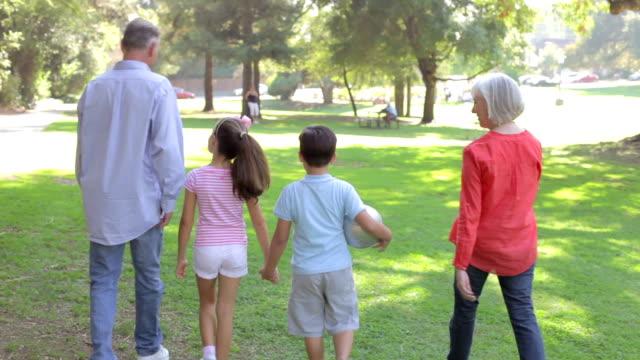 Grandparents-Walking-With-Grandchildren-Through-Park