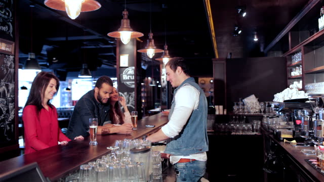 Two-cute-girls-and-a-guy-make-an-order-to-the-bartender