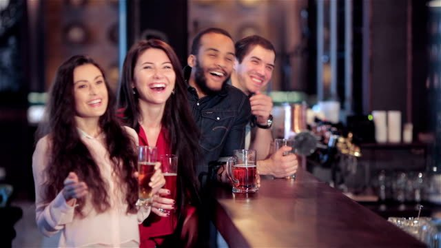 Group-of-girls-and-boys-at-the-bar-cheering-for-their-football-team