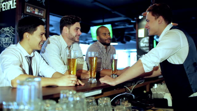 Three-friends-sitting-at-the-bar-and-keep-the-beer