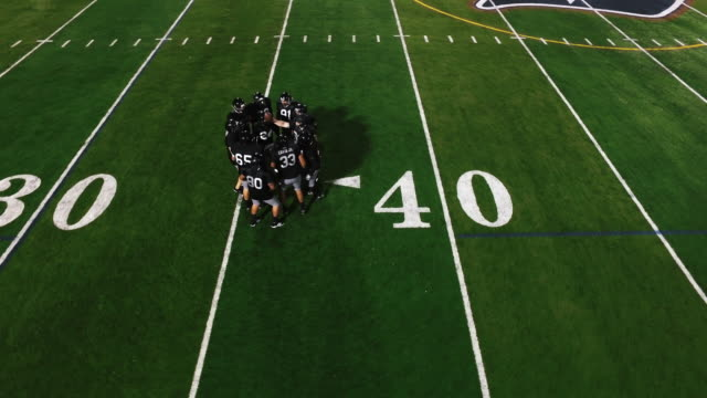 The-camera-spins-from-above-as-a-football-team-in-a-huddle-gets-hyped-and-runs-onto-the-field