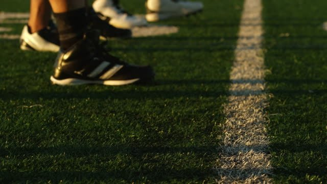 Close-up-of-a-football-player-lining-up-at-the-line-of-scrimmage