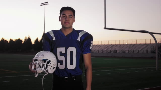 Portrait-of-a-football-player-on-a-field-holding-his-helmet