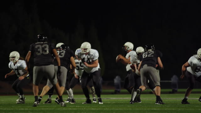 A-football-is-snapped-during-a-game-and-then-thrown-toward-the-camera-to-a-teammate-at-night