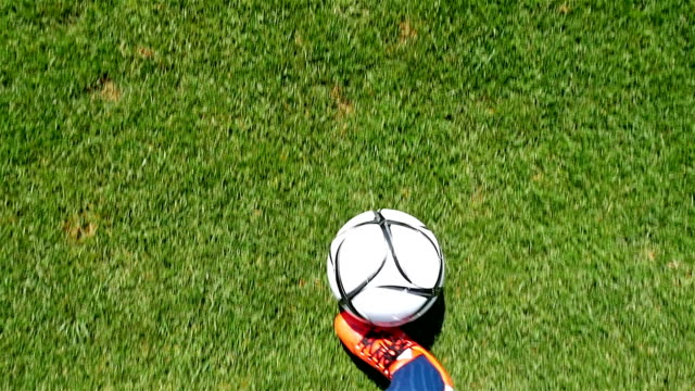 Footballer-leading-the-ball-on-a-football-field-slow-motion