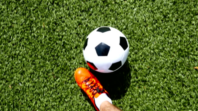 Footballer-with-orange-shoes-leading-the-ball-top-view