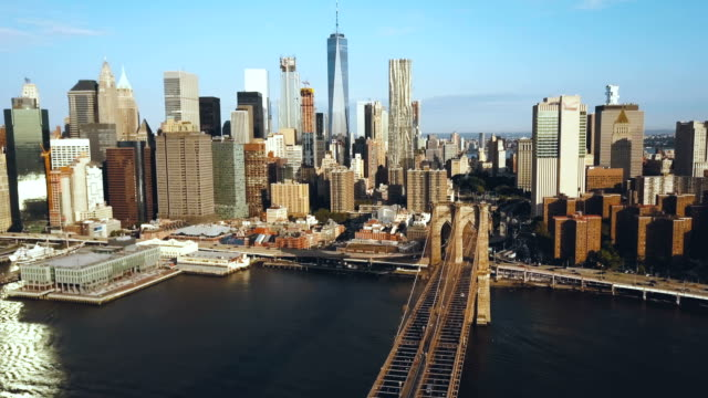 Aerial-view-of-the-Brooklyn-bridge-in-New-York-USA-going-to-the-Manhattan-district-American-flag-waving-on-the-wind