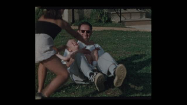 Vater-spielen-mit-Kindern-draußen-im-Garten-Rasen