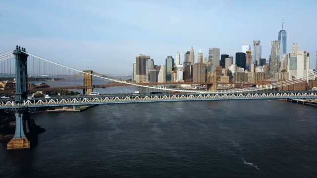 Aerial-view-of-the-skyscrapers-in-downtown-in-New-York-America-Manhattan-bridge-going-through-the-East-river