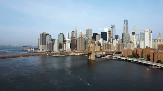 Aerial-view-of-the-capital-of-America-New-York-Drone-flying-up-to-the-Brooklyn-bridge-through-the-East-river