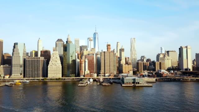 Vista-aérea-de-la-famosa-ciudad-Nueva-York-América-Zánganos-sobrevolando-el-río-East-y-barco-a-través-de-Manhattan