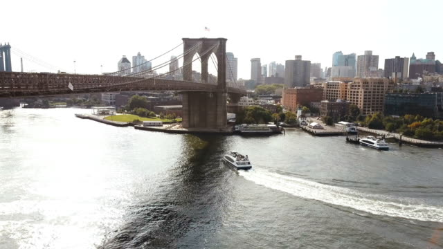 Aerial-view-of-New-York-America-Drone-flying-over-the-East-river-boat-riding-through-the-water-under-Brooklyn-bridge