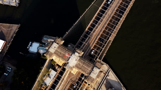 Aerial-top-view-of-Brooklyn-bridge-with-American-flag-on-it-Scenic-view-of-East-river-in-New-York-America