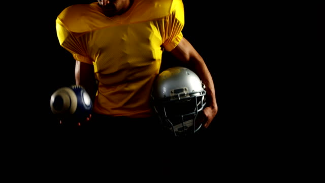 American-football-player-holding-head-gear-and-juggling-ball-4k