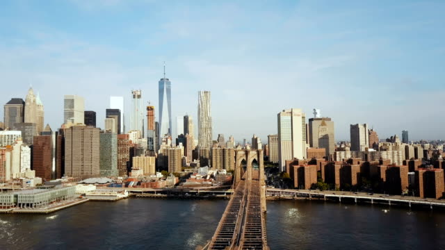 Aerial-view-of-Brooklyn-bridge-with-American-flag-waving-on-the-wind-Scenic-view-of-East-river-Manhattan-in-New-York