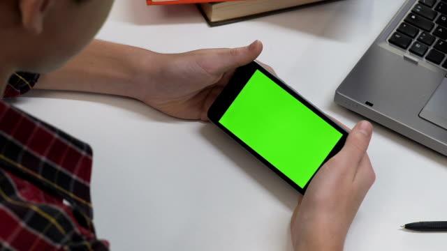 Deporte-ver-niño-en-hogar-smartphone-gadget-adicción-pantalla-verde