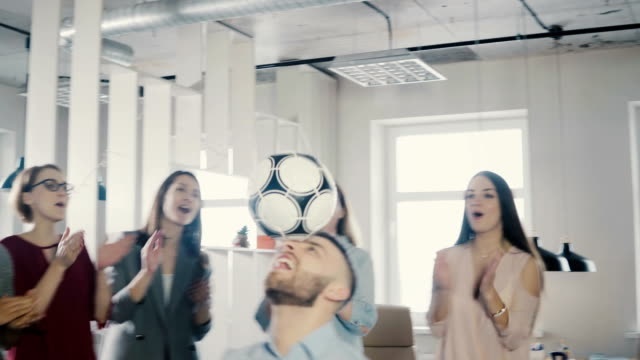 Happy-Caucasian-worker-juggling-football-on-head-Cheerful-mixed-race-executives-celebrate-business-success-in-office-4K