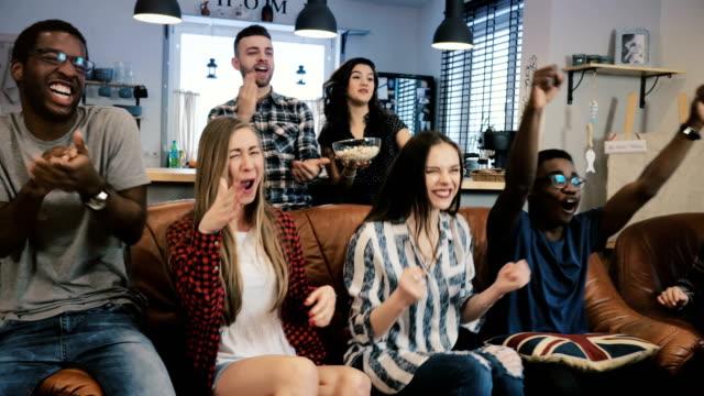 Los-aficionados-al-fútbol-y-multiétnica-celebran-ganar-Slow-motion-4K-Los-fanáticos-van-loco-viendo-juego-de-deportes-en-la-TV-Emoción