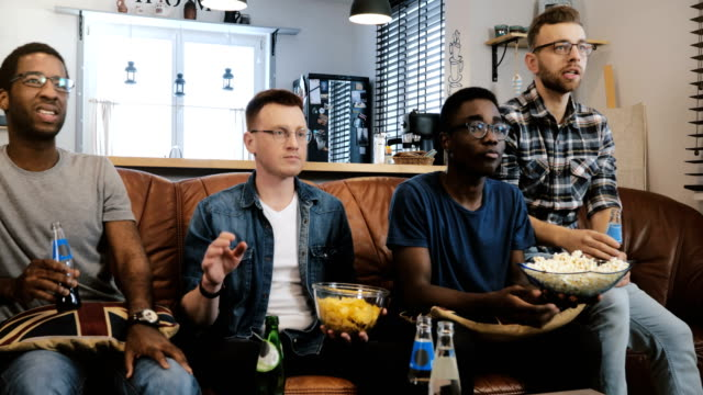 African-American-male-friends-watch-sports-on-TV-Multi-ethnic-geeky-fans-concentrated-and-serious-on-couch-with-popcorn