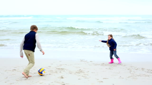 Siblings-playing-football-on-the-beach