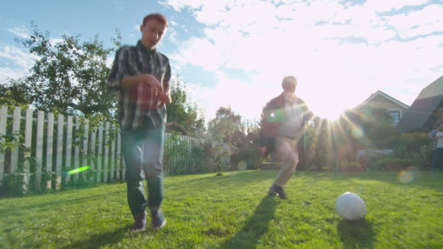 Grandfather-and-Grandson-Play-Football-in-the-Backyard-