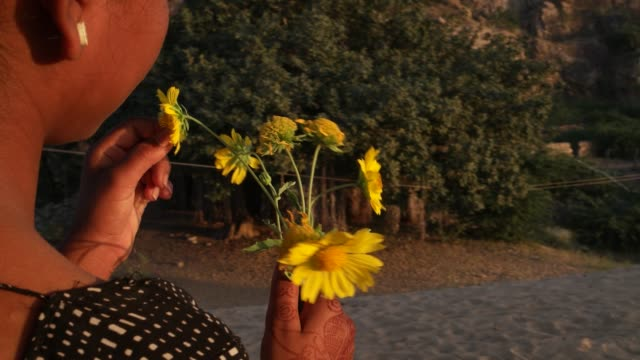 Indian-teenager-beautiful-girl-with-flowers-yellow-waiting-at-a-hill-top-under-a-tree-on-a-summer-day-in-love-happy-joy-sun-tropical-hot-bright-sunshine-content-looking-at-camera-handheld-stabilized
