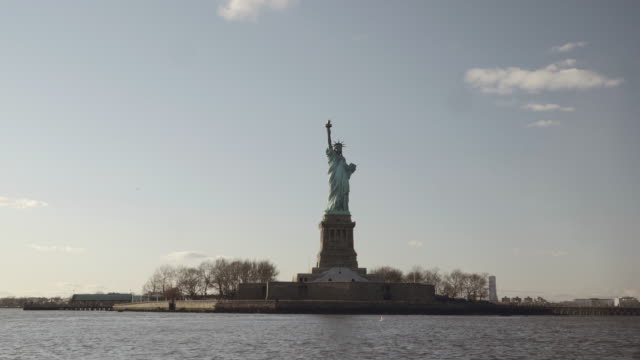 Semi-wide-shot-of-Statue-of-Liberty-filmed-in-the-sunset-from-the-river-in-New-York-United-States-of-America