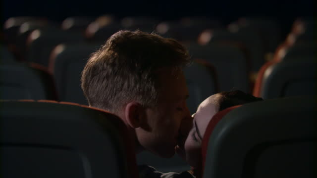 Young-people-kiss-passionately-in-empty-cinema-hall-Love-couple-kissing