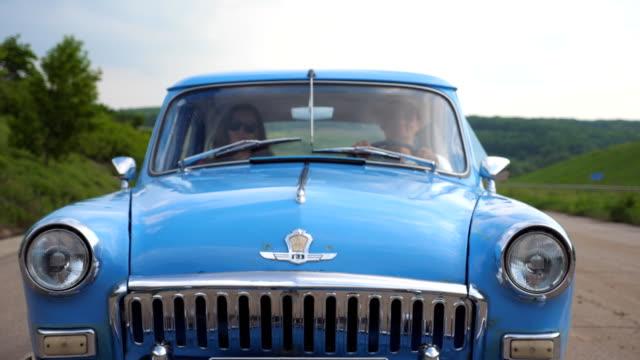 Junges-Paar-in-Hüte-Reiten-in-Oldtimer-im-Sommer-Reisen-Mann-und-Frau-sitzen-am-vorderen-Sitz-des-alten-Retro-Auto-während-der-Fahrt-Konzept-der-Roadtrip-an-Feiertagen-Slow-Motion-vorne-Ansicht-schließen