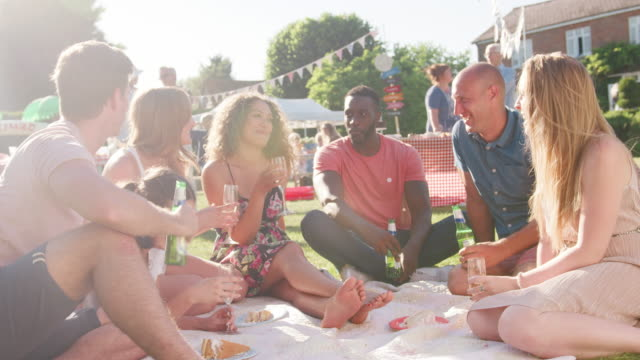 Group-of-friends-eating-and-drinking-as-they-sit-on-rug-at-summer-garden-fete---shot-in-slow-motion