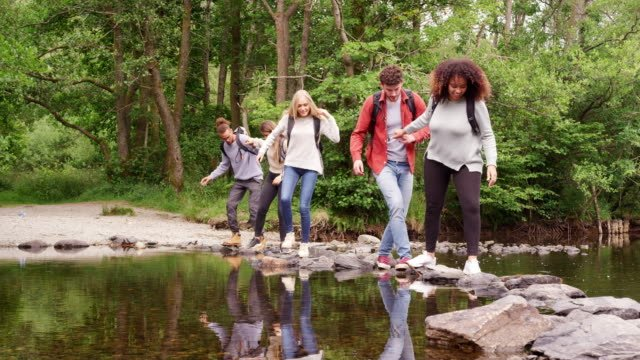 Five-young-adult-friends-hold-hands-and-help-each-other-while-crossing-a-stream-and-standing-on-stones-during-a-hike