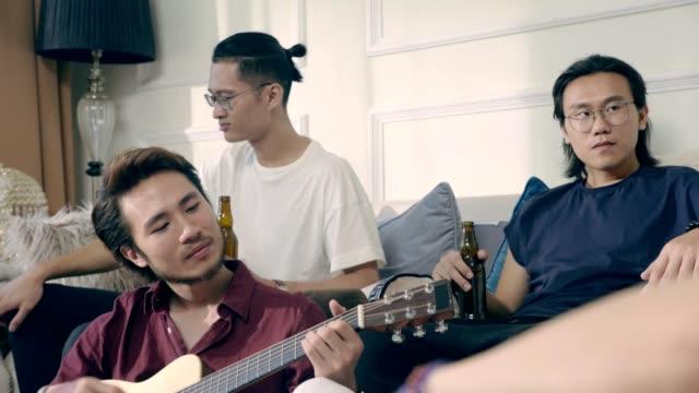 Grupo-de-joven-músico-asiático-reunión-bebiendo-cerveza-en-casa