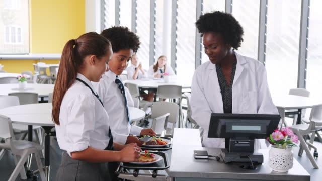Estudiantes-de-secundaria-con-uniforme-pagar-comida-en-cafetería