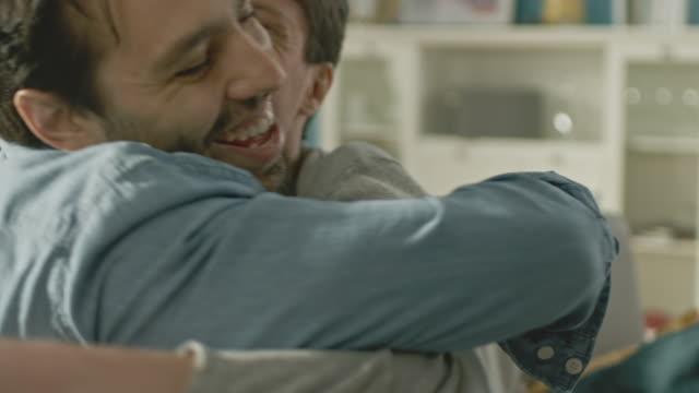 Nette-attraktive-männliche-Gay-paar-sitzen-zusammen-auf-dem-Sofa-zu-Hause-Freunde-sind-Hugging-und-umarmen-einander-Sie-sind-glücklich-und-Lächeln-Sie-sind-lässig-gekleidet-und-Zimmer-ist-Modern-eingerichtet-