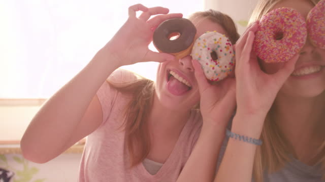Adolescent-girls-with-colourful-doughnuts-over-their-eyes