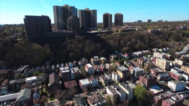 Cliffside-Park-NJ-vuelo-sobre-casas-a-edificios-de-apartamentos-con-cielo-azul