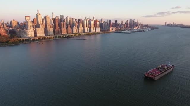 NYC-Aerial-Shot-Fly-Backwards-Shot-Of-Upper-Westside-With-Red-Tug-Boat