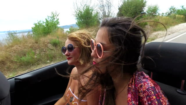 Two-carefree-girls-partying-while-riding-in-cabriolet