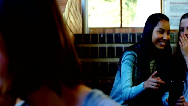 School-friends-bullying-a-sad-girl-in-school-corridor