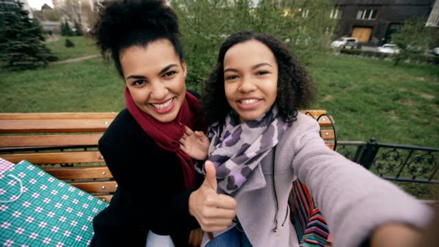 Dos-linda-mujer-afroamericana-tomando-selfie-en-smartphone-con-bolsas-de-compras-y-sonriente-Sentado-en-el-Banco-de-la-calle-novias-divertirse-después-de-visitar-el-centro-comercial-ventas
