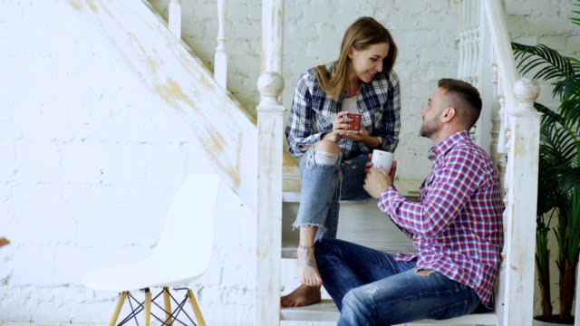 Young-happy-and-loving-couple-drink-tea-and-talking-while-sitting-on-stairs-in-living-room-at-home