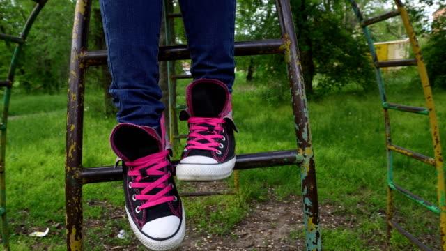 Pies-femeninos-en-zapatillas-moviéndose-y-posando-en-el-parque-de-primavera-