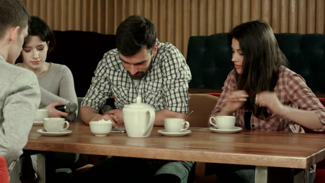 Group-of-young-people-sitting-at-a-cafe-talking-and-drinking-tea