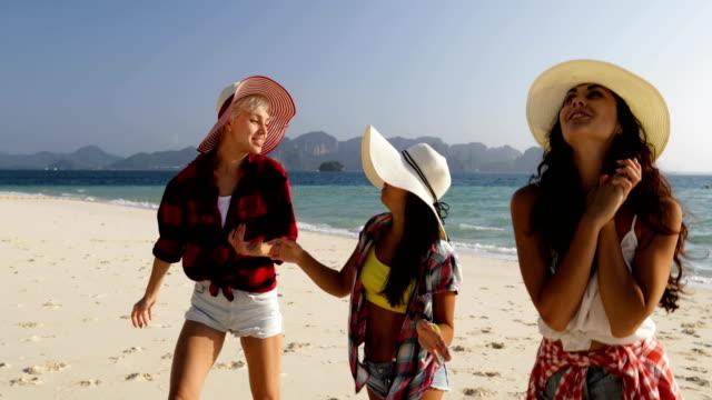 Mujer-habla-a-pie-de-agua-en-la-playa-las-chicas-jóvenes-turistas-comunicación-feliz-sonriendo