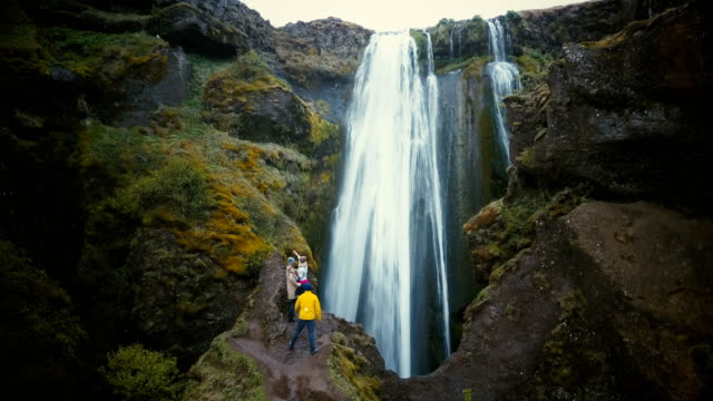 Aerial-view-of-the-group-of-tourists-enjoying-the-view-of-Gljufrabui-waterfall-in-Iceland-Friends-happy-after-hiking