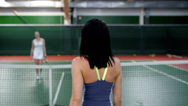 Zwei-schöne-Frauen-die-einander-nach-dem-Spiel-zu-danken-Professionellen-Tennisspielerinnen-der-Diskussion-über-das-Spiel-im-Erholungsgebiet-Sportlerinnen-die-Verlängerung-der-Anerkennung-für-ein-erfolgreiches-training