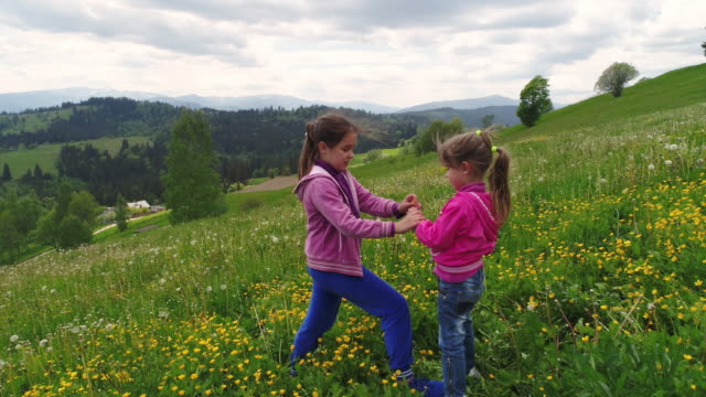 Children-playing-on-a-flowering-lawn-against-the-backdrop-of-the-Carpathian-Mountains